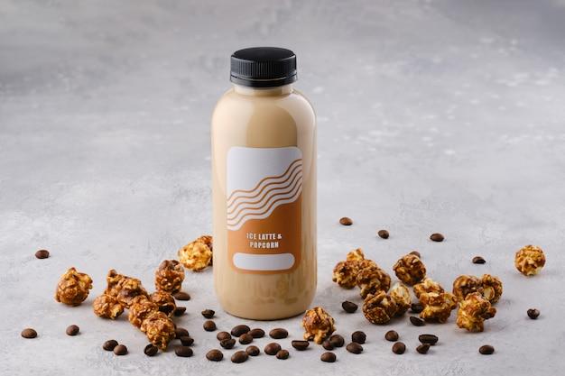 Pequena garrafa com coquetel de café com leite e pipoca em cima da mesa