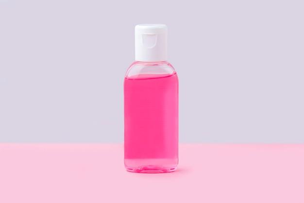 Pequena garrafa com gel desinfetante anti-séptico para lavar as mãos no fundo rosa. gel de álcool como prevenção de coronavírus. conceito de prevenção de doenças virais.