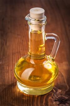 Pequena garrafa com óleo de girassol na prancha de madeira velha