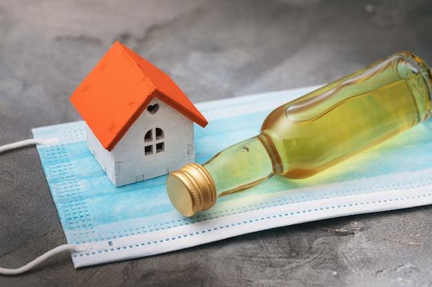 Pequena garrafa de uísque e máscara médica da casa de brinquedo na mesa
