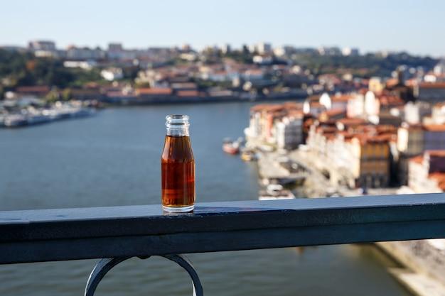 Pequena garrafa de vinho do porto ao ar livre com o rio douro e cidade do porto
