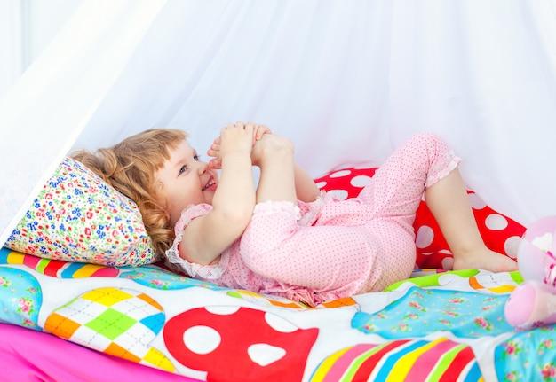 Pequena gata encaracolada em pijama rosa deitada em uma cama de bebê