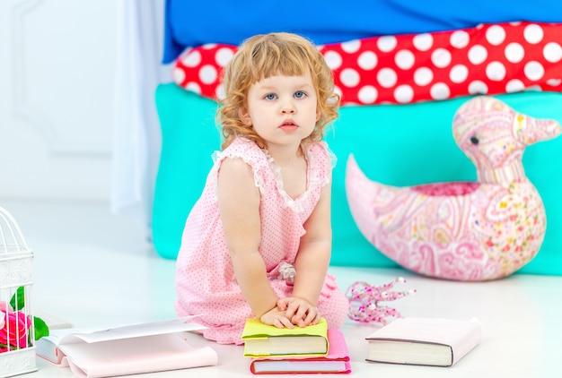 Pequena gata encaracolada em pijama rosa, observando o livro sentado no chão