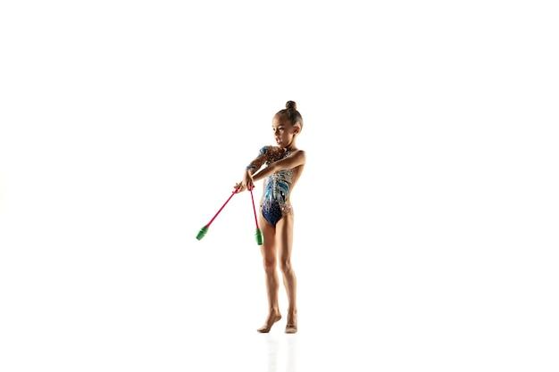 Pequena ginasta feminina e flexível isolada na parede branca