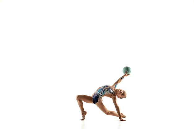 Pequena ginasta feminina flexível isolada na parede branca