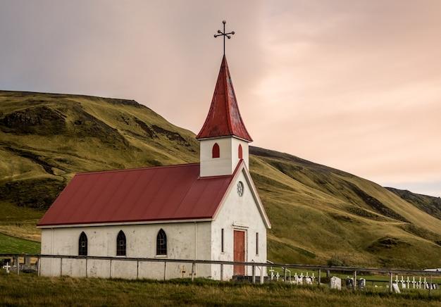Pequena igreja branca com telhado vermelho reyniskyrka em vik islândia
