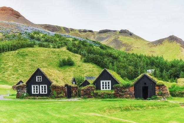 Pequena igreja de madeira e cemitério na islândia. pôr do sol cênico através de coroas de árvores