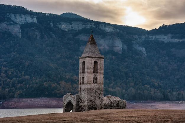 Pequena igreja em ruínas com a sua torre sineira na frente de montanhas e ao lado de um rio na catalunha, espanha