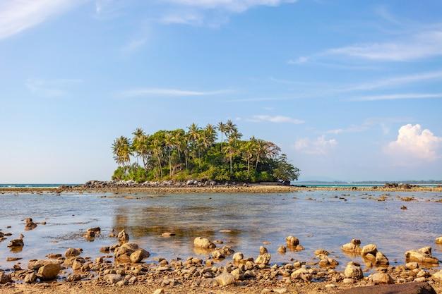 Pequena ilha em um mar tropical com fundo azul do oceano e céu azul com nuvens brancas