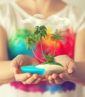 Pequena ilha fantástica com palmeiras tropicais nas mãos das mulheres