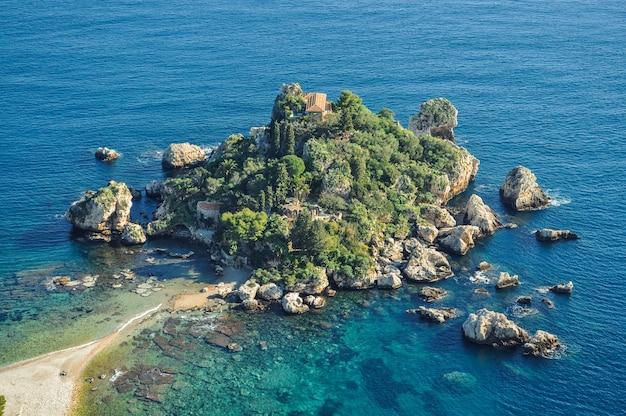 Pequena ilha rochosa cercada por águas azuis na costa da grécia, europa