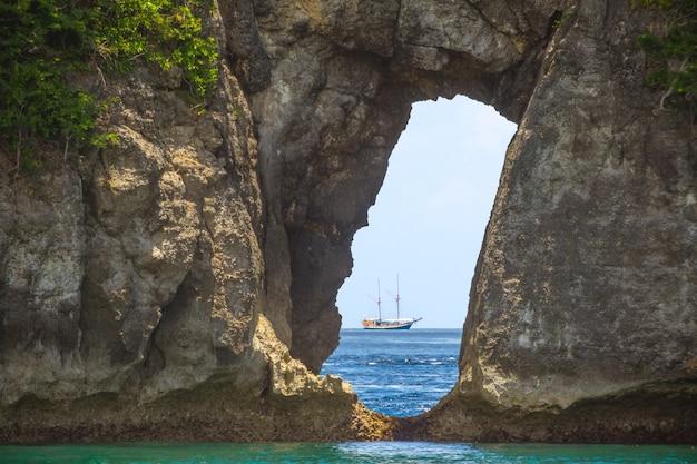 Pequena ilha rochosa. um veleiro no horizonte é visível através de um arco de pedra