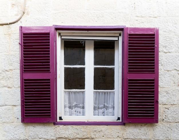 Pequena janela com persianas roxas