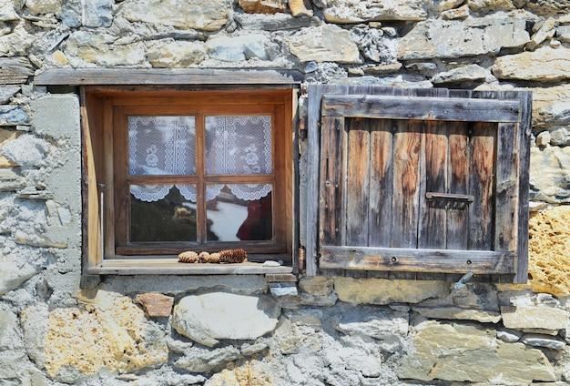 Pequena janela e obturador em uma fachada chapada de um antigo chalé alpino