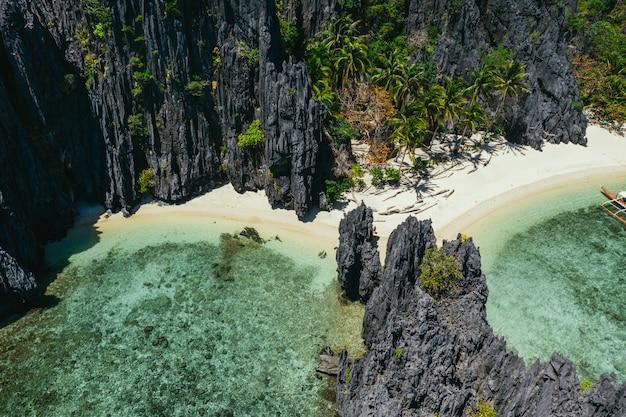 Pequena lagoa em el nido. pessoas andando na areia branca, com selva tropical. conceito sobre viagens e natureza