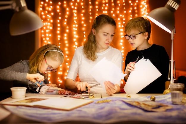 Pequena loira e menina e sua mãe escreve a carta para o papai noel