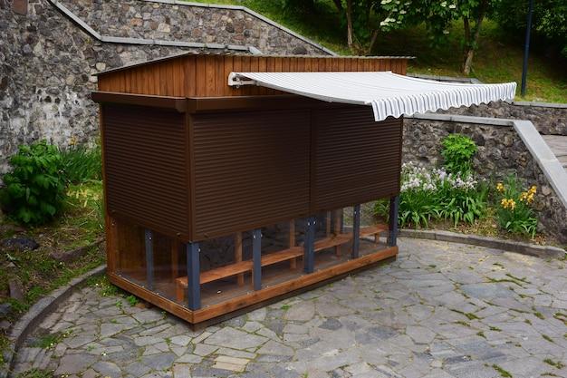 Pequena loja de comércio de madeira com marquise. as janelas são fechadas com persianas. ninguém