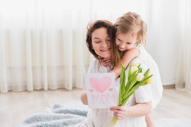 Pequena menina abraçando a mãe de costas enquanto sorrindo mãe segurando o cartão e flores em casa