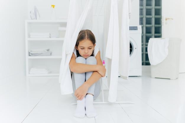 Pequena menina adorável senta-se no chão
