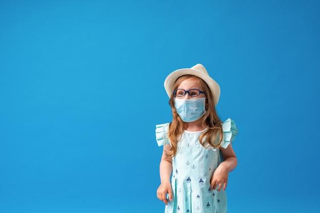 Pequena menina alegre em óculos, chapéu e poses de vestido de verão