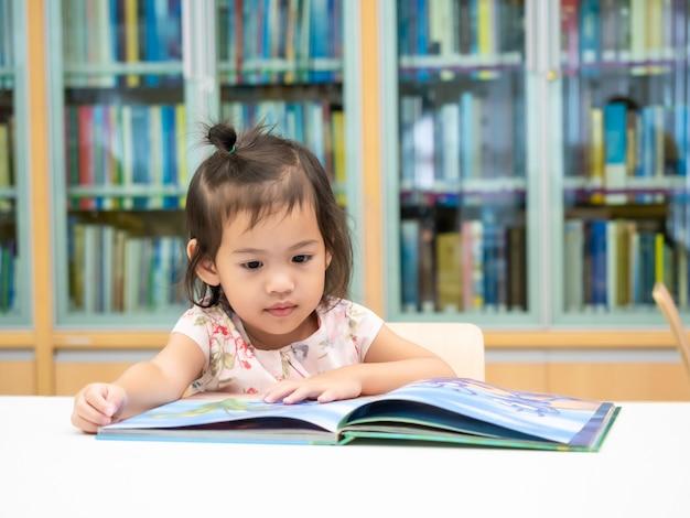 Pequena menina asiática bonita 3-4 anos sentado na cadeira e olhando o livro infantil na biblioteca.