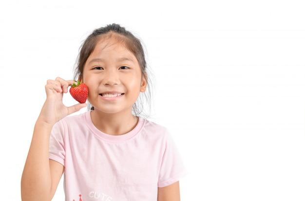 Pequena menina asiática bonita segurando um morango
