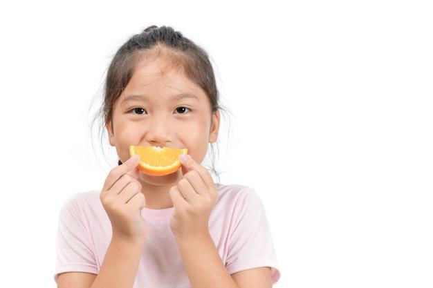 Pequena menina asiática bonito segurando uma laranja em fatias