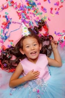 Pequena menina asiática, chapéu de aniversário, sorriso, presente, confete, deitada de costas, vista superior,