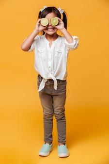 Pequena menina bonito, cobrindo os olhos com limão.