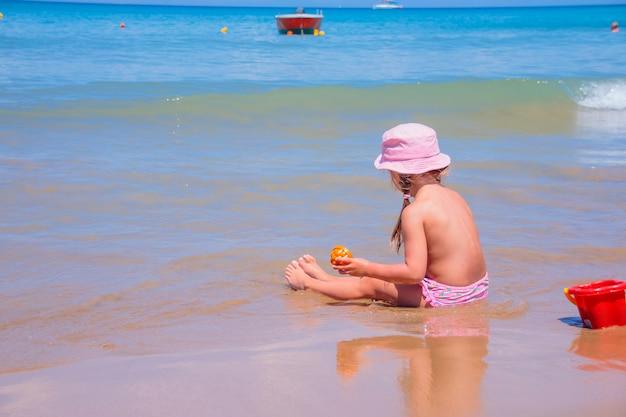 Pequena menina brincando na praia com um balde vermelho e pá. uma criança bebê ssitting na água sozinha com chapéu de sol em um dia ensolarado de verão. criança brincando com brinquedos de praia na praia tropical. copie o espaço
