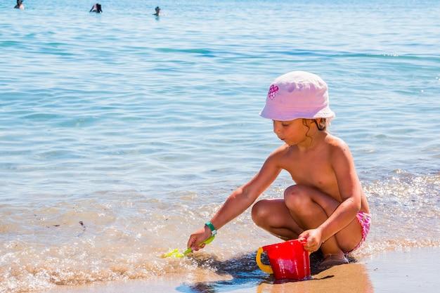 Pequena menina brincando na praia com um balde vermelho e pá. uma criança bebê ssitting na água sozinha com chapéu de sol em um dia ensolarado de verão. criança brincando com brinquedos de praia na praia tropical.