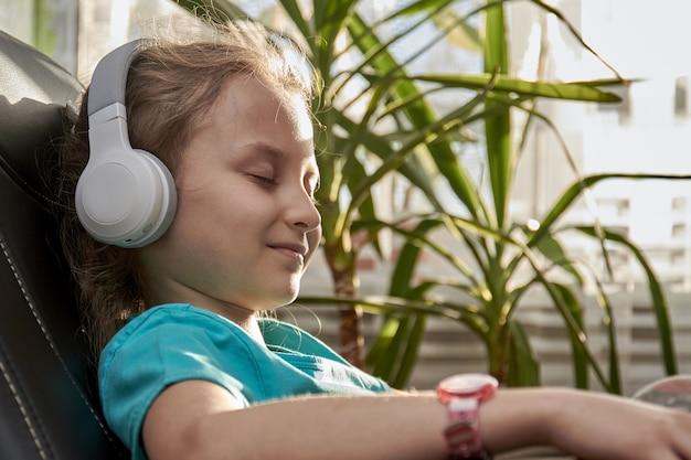 Pequena menina caucasiana em fones de ouvido senta na poltrona preta e ouvindo música. fone de ouvido sem fio