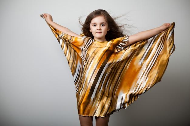 Pequena menina com cabelo comprido em vestido listrado dourado com bainha larga sobre fundo cinza