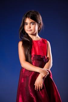 Pequena menina com cabelo comprido em vestido vermelho dourado