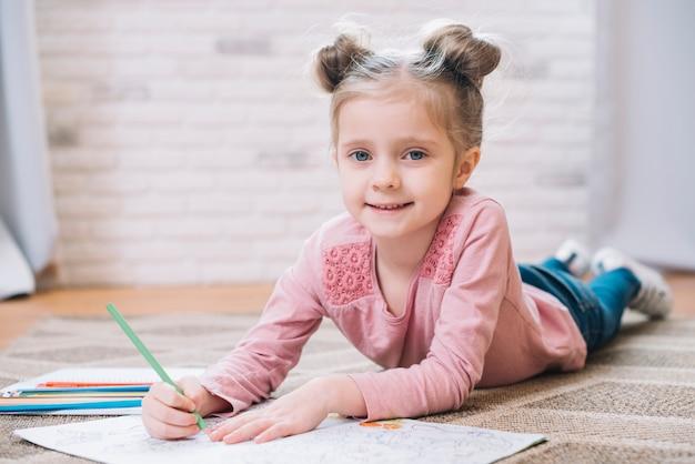 Pequena menina cute desenho no livro deitado no tapete em casa