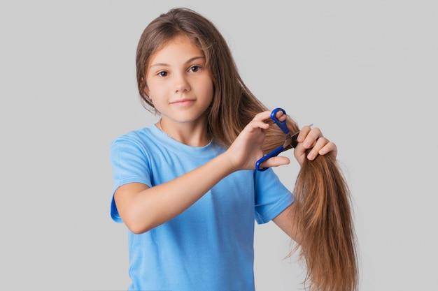 Pequena menina de bochecha de maçã em uma camiseta azul vai cortar seus longos cabelos
