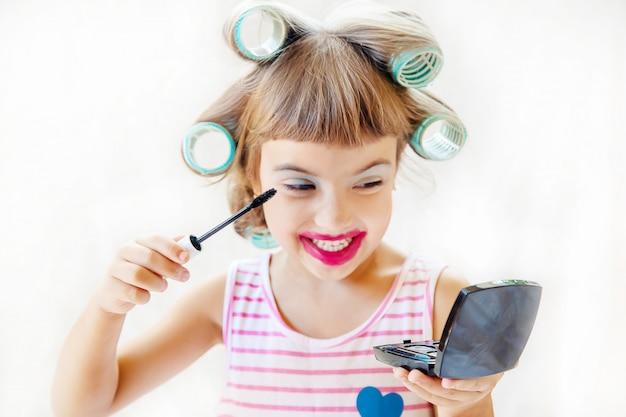 Pequena menina de moda. garota faz a maquiagem e manicure. foco seletivo.