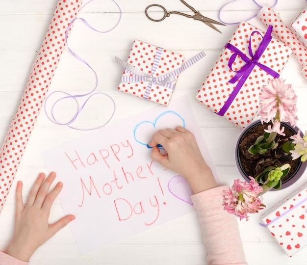 Pequena menina desenhando um cartão de felicitações