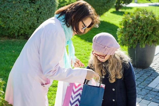Pequena menina e mãe feliz e olhando para compras