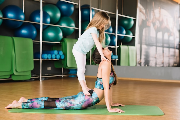 Pequena menina em pé na mãe dela fazendo exercício no ginásio