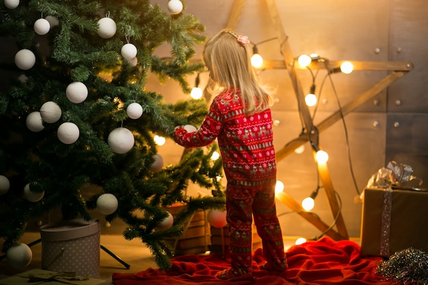 Pequena menina em pijama pela árvore de natal