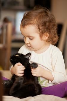 Pequena menina encaracolada bonita, segurando um gato preto na mão.