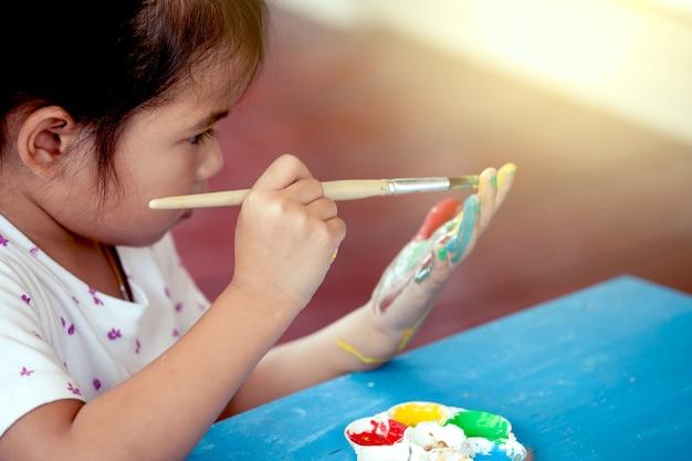 Pequena menina está pintando sua mão
