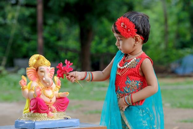 Pequena menina indiana com senhor ganesha e rezar