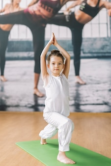 Pequena menina inocente fazendo yoga no ginásio