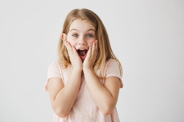 Pequena menina loira de olhos azuis, segurando o rosto com as mãos e boca aberta, expressando emoção. garoto ficando feliz depois de receber o presente de aniversário da mãe.