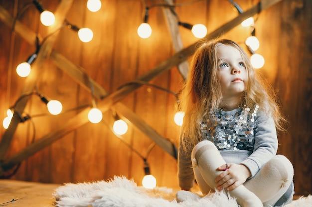 Pequena menina loira sentada no chão