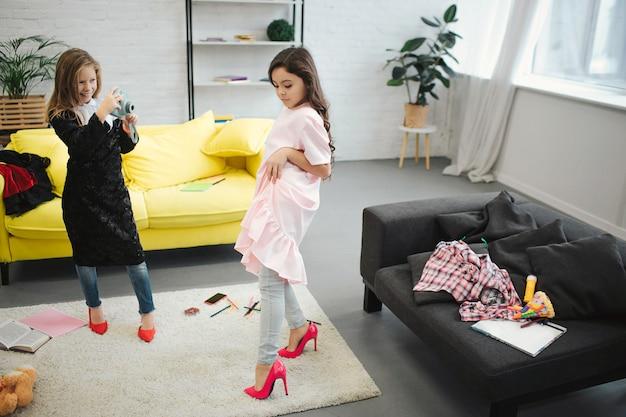 Pequena menina loira tirando foto de sua amiga no quarto. morena posando e olhando para baixo. ambos os adolescentes usam roupas e sapatos para mulheres adultas.