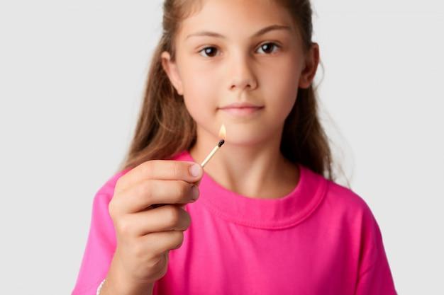 Pequena menina segurando fósforo aceso