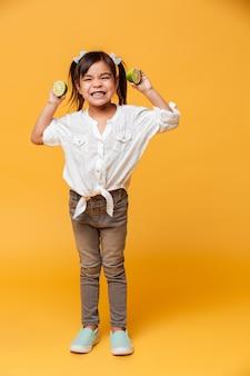 Pequena menina segurando limão.